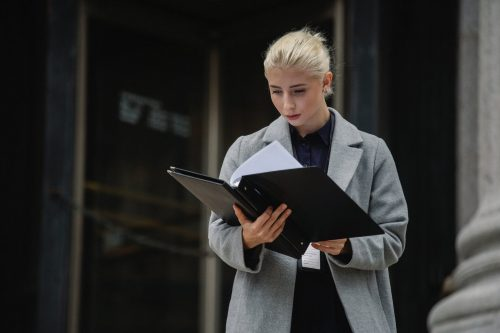 lady reading documents outside